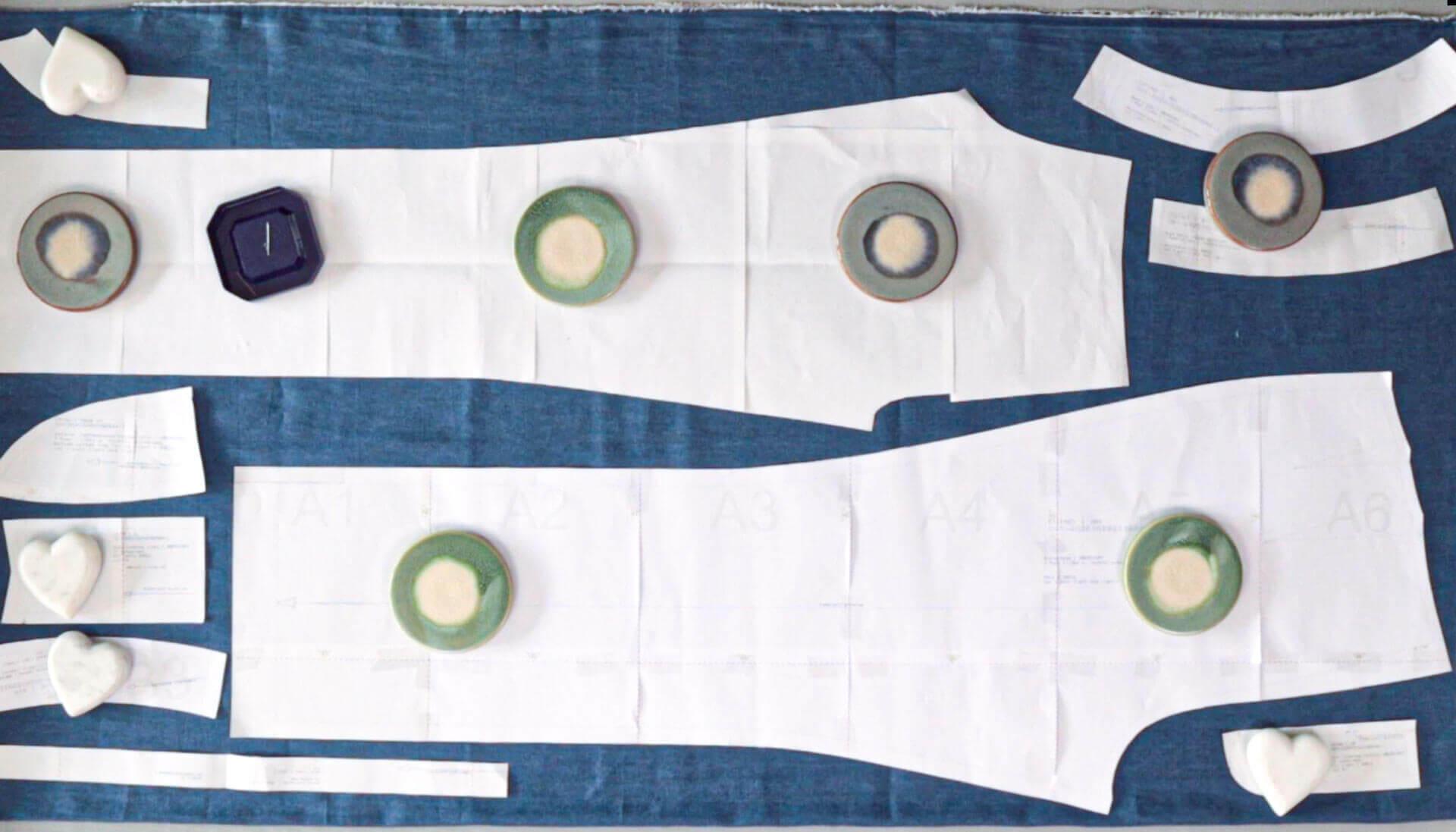 positionierte Schnitteile mit Stecknadeln oder Gewichten auf dem Stoff vor dem Verrutschen sichern