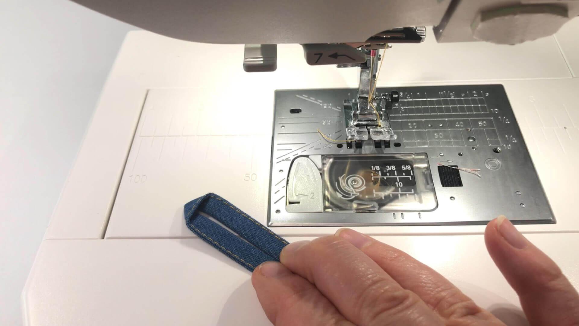 Nähanleitung Paspeltasche - Knopfschlaufe steppen und falten